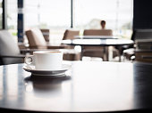 Coffee cup on table with blurred people in Restaurant shop cafe Interior seats background