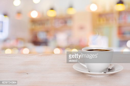 Coffee cup on wooden table over defocused cafeteria background : Stock Photo