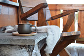 Dark green coffee cup outside on mountain lodge porch with reindeer skins and chair.