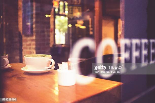 Coffee Cup Seen Through Glass Window Of Cafe