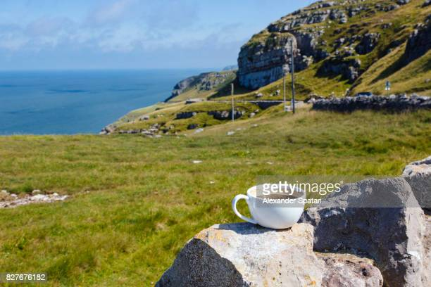 Coffee cup standing on the rock overlooking beautiful landscape at Great Orme, Llandudno