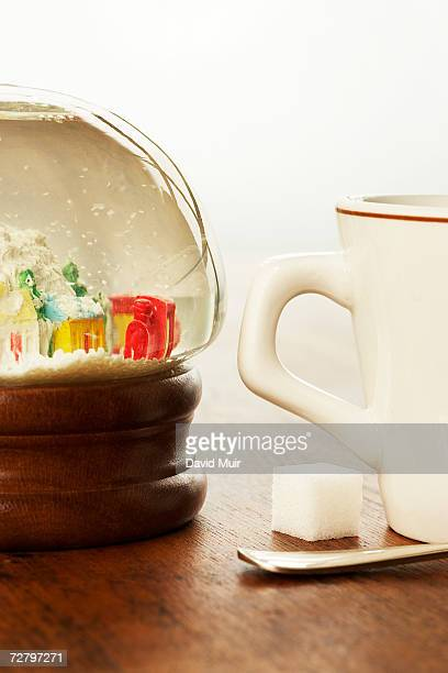 Coffee cup, sugar cube and snow globe on table, close-up