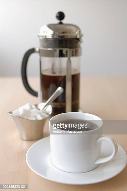 Coffee cup, sugar cubes and french coffee press on table
