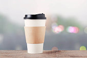 Coffee cup on wooden floor with bokeh background.