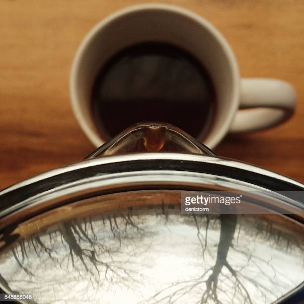 Coffee cup with coffee pot and reflection