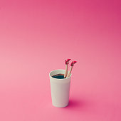 Coffee cup with female doll legs on pink background. Coffee concept.