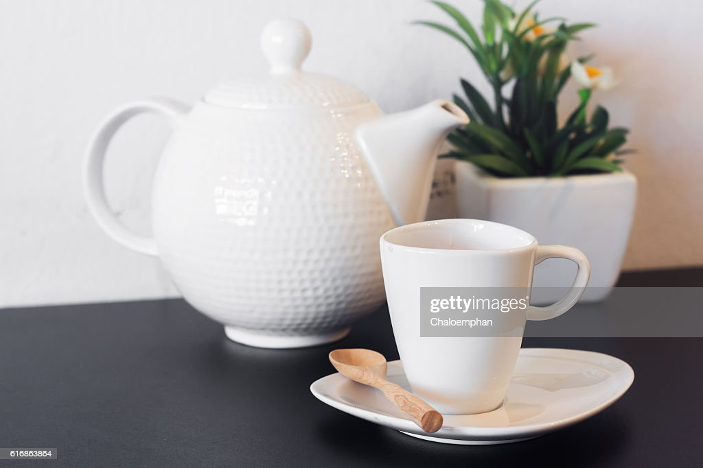 coffee cup with pitcher on black table against white : Stock Photo