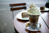 Coffee cup with whipped cream topping on table