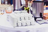 Coffee, cups on catering table at conference or wedding banquet. Group of empty white ceramic cups for coffee or tea in outside buffet at the business meeting event or hotel.