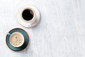 Coffee cups on wooden kitchen table. Top view with copyspace for your text