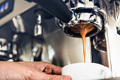 Close up of coffee being brewed by the machine flowing through portafilter into the cup at cafe