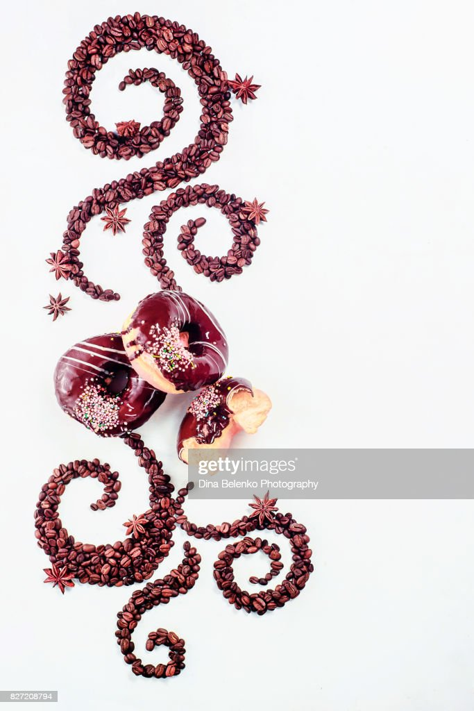 Coffee grains lying in the shape of a swirl with cinnamon, anise stars and donuts : Stock Photo