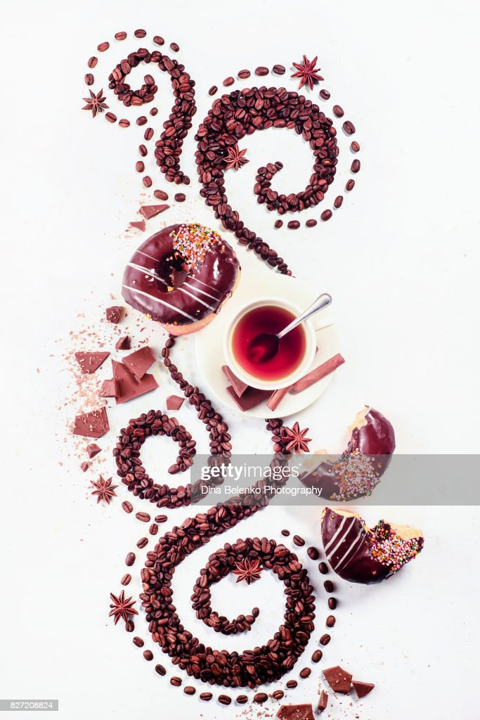 Coffee grains lying in the shape of a swirl with the cup, cinnamon, anise stars and donuts : Stock Photo