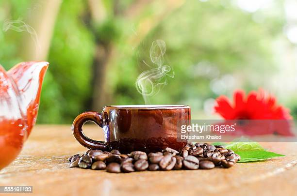 Coffee in a mug & beans with flower and leaves