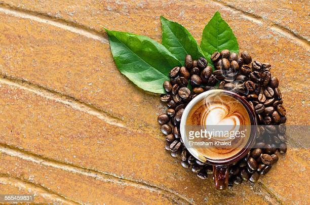 Coffee in a mug with coffe beans &  leaves top vie