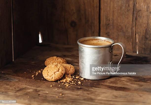 Coffee in aluminum mug with amaretti biscuits