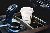 Coffee in the car salon. A single paper coffee cup inside the car cup holder. transport concept - close up.