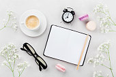 Coffee, cake macaron, clean notebook, eyeglasses, alarm clock and flower for cozy breakfast on light table top view. Woman working desk. Flat lay style.