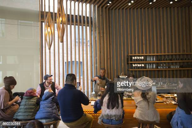 A coffee master center prepares a specialty drink for customers at the Starbucks Reserve Roastery and Tasting Room in Seattle Washington US on Monday...