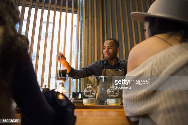 A coffee master prepares a specialty drink for customers at the Starbucks Reserve Roastery and Tasting Room in Seattle Washington US on Monday Oct 9...
