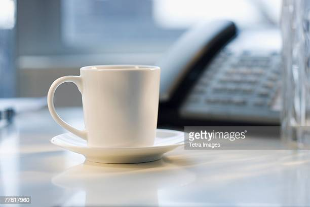 Coffee mug and saucer on desk