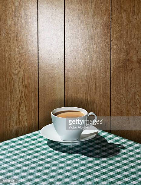 Coffee mug on checkered tablecloth