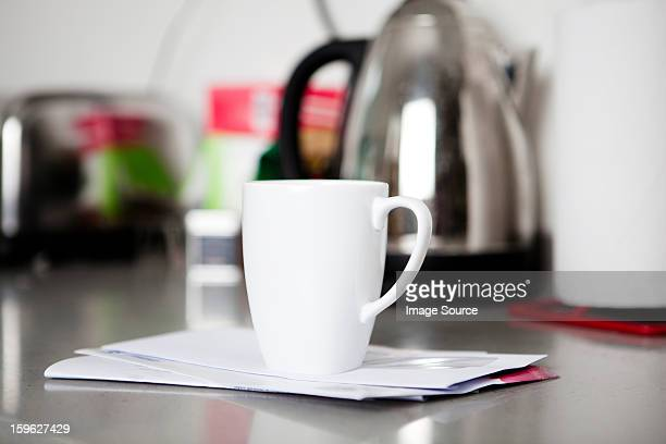 Coffee mug on top of envelopes