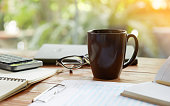 Coffee mug and business objects on wooden desk with greenery background, selective focus