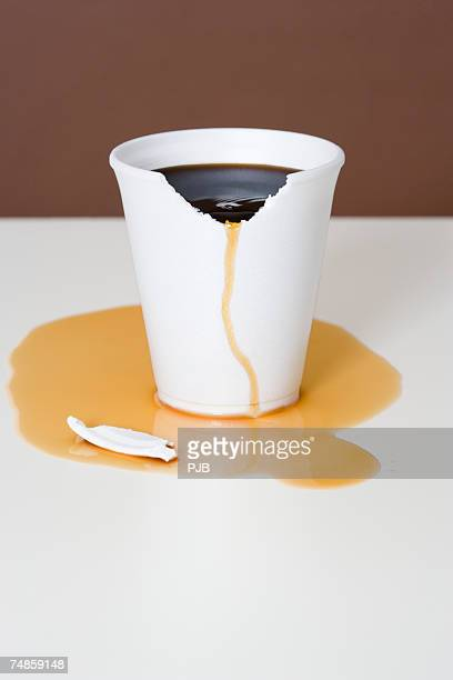 Coffee overflowing from chewed styrofoam cup