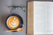Top view of a cup of Latte coffee with open book and eye glasses