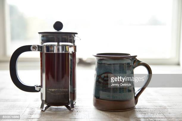 Coffee plunger and mug on table