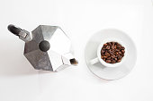 Coffee pot and roasted coffee beans into the cup from above