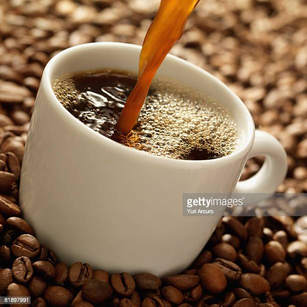 Coffee pouring into mug surrounded by coffee beans