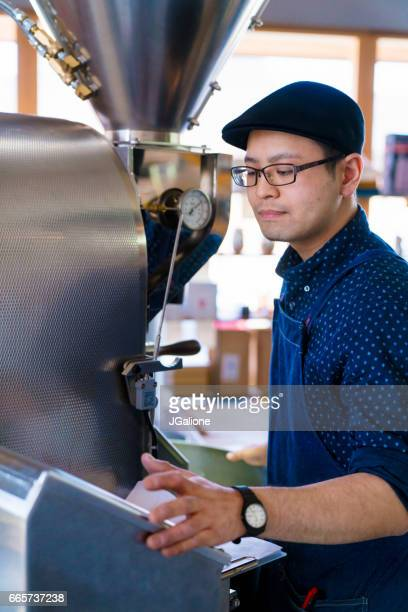 Coffee roaster checking on his settings as he roasts beans