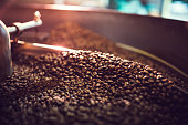 The process of roasting a batch of high quality single origin coffee beans in a large industrial roaster; the toasted beans are in the cooling cycle.  Horizontal image with copy space.  High contrast