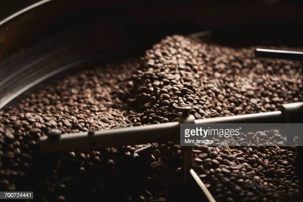 A coffee shop. A drum of roasting coffee beans.