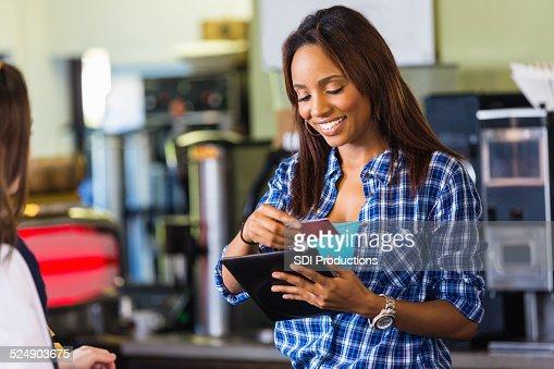 Coffee shop cashier swiping card on digital tablet reader