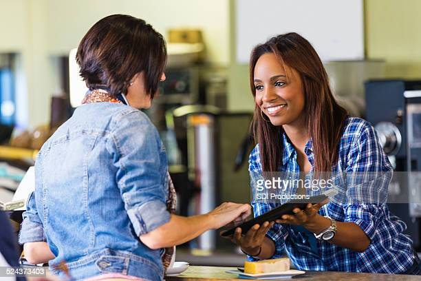 Coffee shop customer signing digital credit card receipt on tablet
