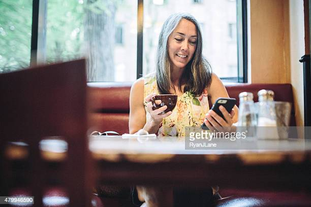 Coffee Shop Mature Woman Using Her Smartphone And Drinking