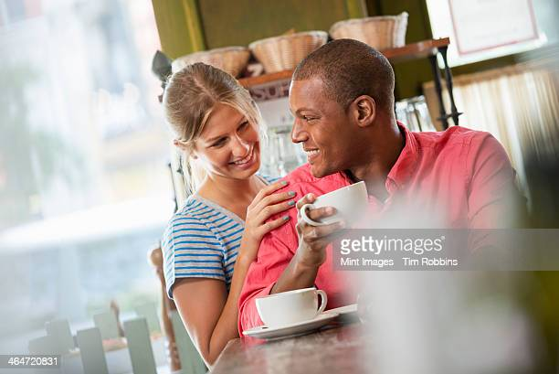 A coffee shop or cafe in the city. Two people, a man and woman seated close together, looking at each other. Having a cup of coffee.