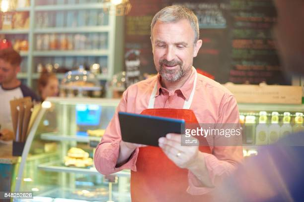 coffee shop owner taking an order on a tablet