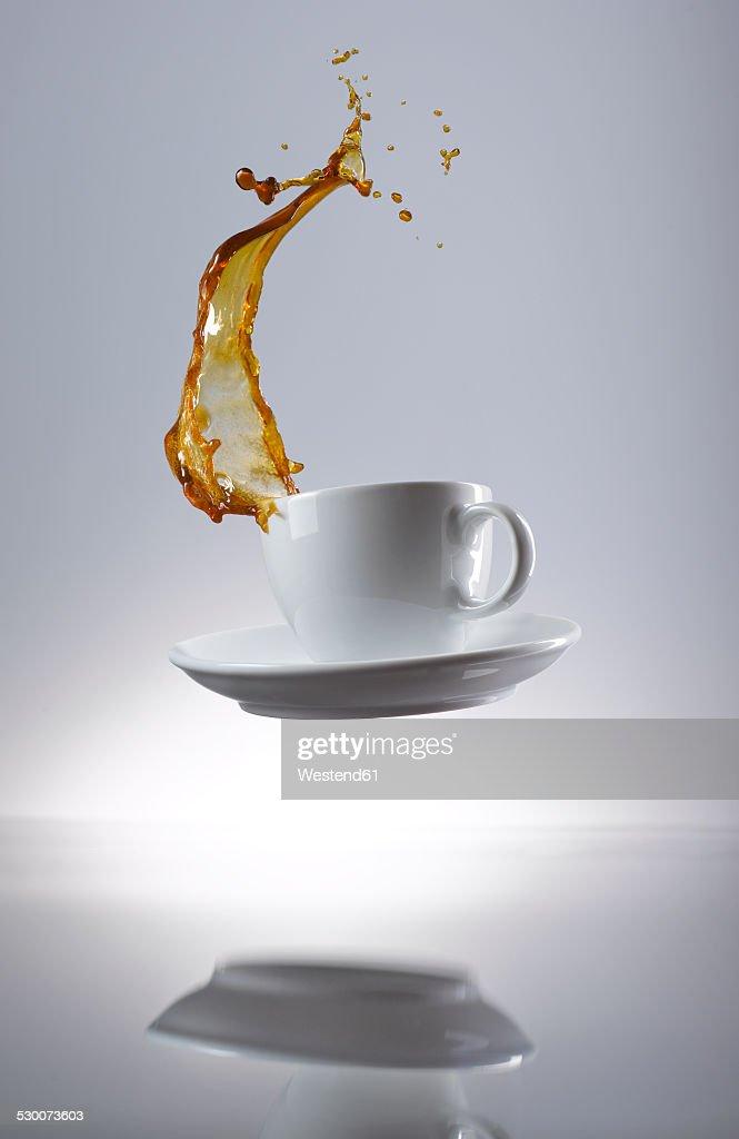 Coffee splashing in cup