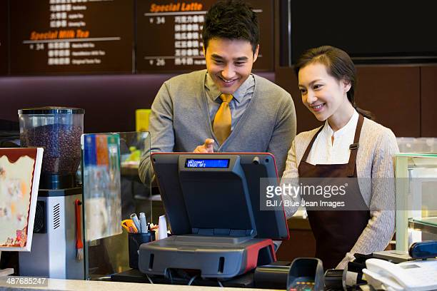 Coffee store shopkeeper and waitress using cash register