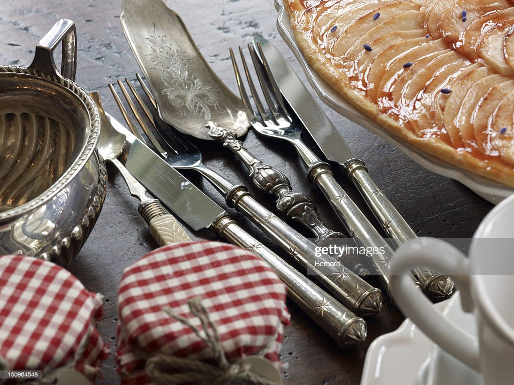 Coffee table with apple tart and antique silverware