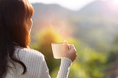 Woman drinking hot coffee outdoor enjoying sunrise and landscape during vacation on the mountain with rim light effect,holiday concept.