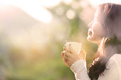 Woman feeling blissful with hands holding coffee cup at sunset light on the mountain, holiday lifestyle.