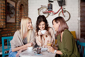 Three women at cafe, talking,smiling,  laughing and enjoying their time. Lifestyle and friendship concepts with real people models.