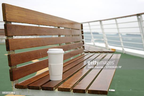 Coffee to go cup on bench on a cruise ship