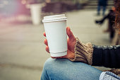 Woman drinking coffe on the street. Close up