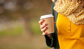 Close up of young woman holding a cup of takeaway coffee cup, shallow depth of field